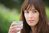 Brunette holding a glass of water — Stock Photo