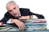 Businessman lying over a pile of documents — Stock Photo