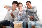 Three male teenagers playing video games. — Foto de Stock