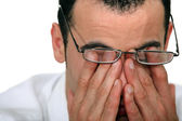 Tired man rubbing his eyes — Stockfoto