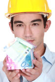 Builder with a house made of money — Stock Photo