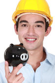 Builder holding piggy-bank — Stock Photo