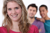 Smiling young woman with lads in the background — Stock Photo