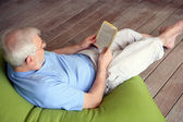 Man on couch reading book — Stock Photo