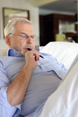 Senior man doing crossword puzzles — Stock Photo