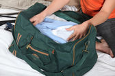Woman puts things into a suitcase — Stock Photo