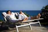 Senior couple on sun lounger whilst on holiday — Stock Photo