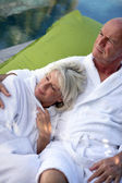 Senior couple lounging in bathrobes — Stock Photo