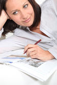 Woman highlighting a newspaper using a pencil — Stock Photo
