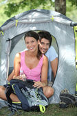 Couple sitting in front of their tent — Stock Photo