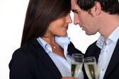 Flirtatious business couple drinking champagne — Stock Photo