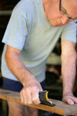 Senior handyman sanding a plank of wood — Stock Photo