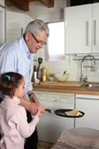 Little girl tossing pancakes with her granddad — Stock Photo