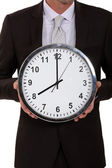 A cropped picture of a businessman holding a clock. — Stock Photo