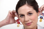 Woman holding baby soothers near her ears — Stock Photo