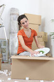 Woman unpacking cardboard boxes — Stock Photo