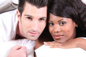Mixed race couple laying in bed — Stock Photo