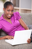 Black woman doing computer and relaxing on a sofa — Stock Photo