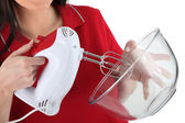 A woman using an electric beater — Stock Photo