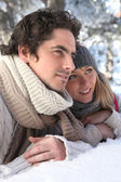 Attractive couple laying in the snow — Stock Photo