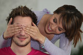 Woman covering boyfriend's eyes — Stock Photo