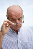 Older man peering over his glasses — Stock Photo
