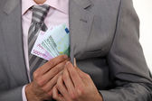 Businessman pulling money out of pocket — Stock Photo