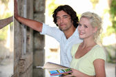 Couple looking at a tourist information board — Stock Photo