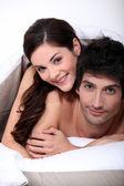 Para w łóżku obejmując — Zdjęcie stockowe