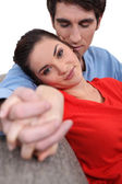 Couple holding hands on a sofa — Stock Photo