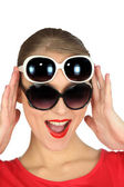 Studio shot of a woman wearing two pairs of sunglasses — Stock Photo