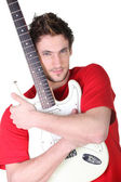 Young man hugging his guitar — Stock Photo