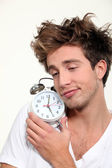 Sleepy man hugging his alarm clock — Stock Photo