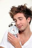 Sleepy man hugging his alarm clock — Stock Photo