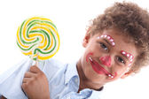 Child made-up with yellow lollipop — Stock Photo