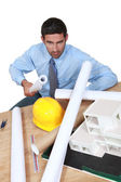 Angry architect sat at his desk — Stock Photo