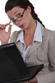 Businesswoman peering over her glasses — Stock Photo