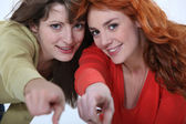 Two female friends pointing at the camera. — Stock Photo