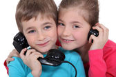 Brother and sister with old fashioned telephone — Stock Photo