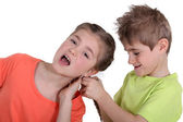 Brother pulling sister's hair — Stock Photo