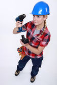 Craftswoman putting a charger in a drill — Stock Photo