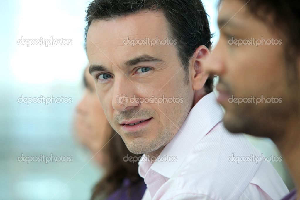 Headshot of a handsome man standing with colleagues in a line — Stock Photo #11846388