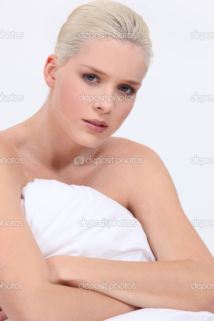 Blonde woman naked sitting on bed with a neutral face expression — Stock Photo #11847022
