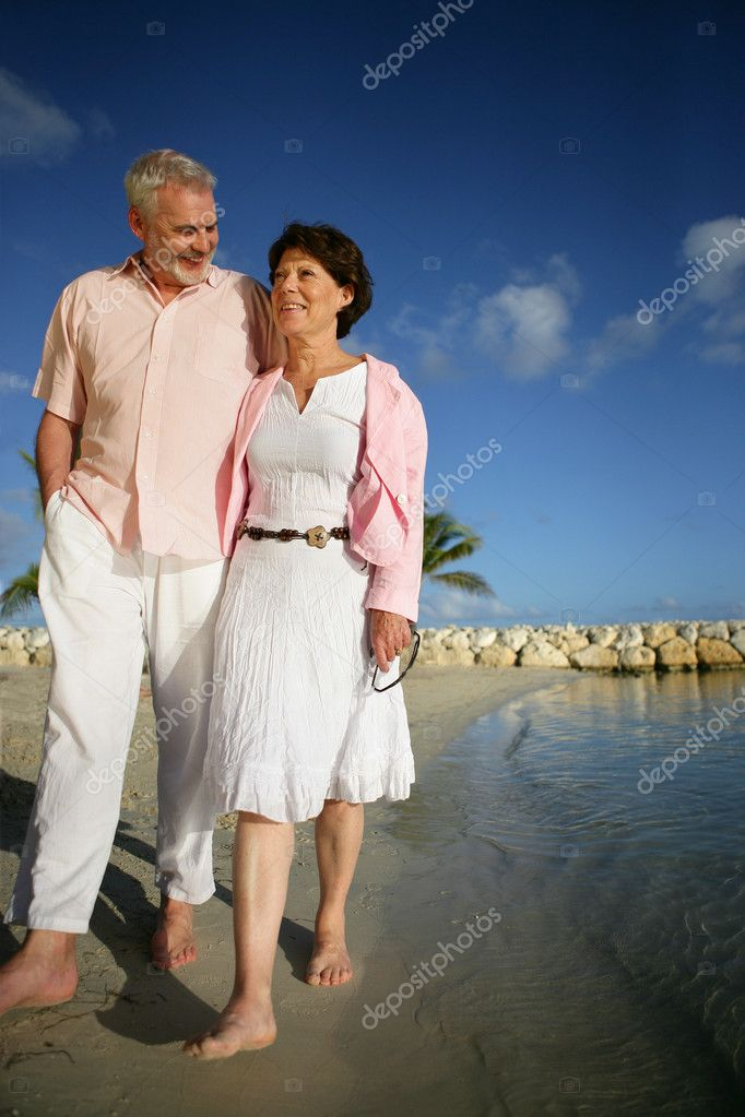 Senior couple walking on the beach  Stock Photo #11847419