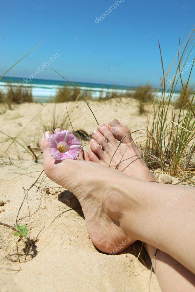 Woman laid on beach flower between toes — Stock Photo #11848141