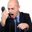 Man shouting angrily in receiver — Stock Photo