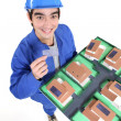 Laborer holding architect model - Stock Photo