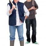 Senior bricklayer and junior apprentice against studio background — Stock Photo