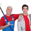Mature painter holding roller with young apprentice — Stock Photo