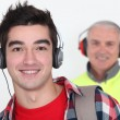 Student wearing headphones in front of a worker wearing ear defenders - Stock Photo